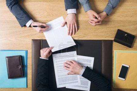 Photo pour Homme et femme d'affaires s'asseyant au bureau des avocats et signant des documents importants, mains vue supérieure, personnes méconnaissables - image libre de droit