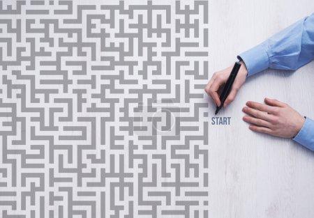 Businessman entering maze and holding marker