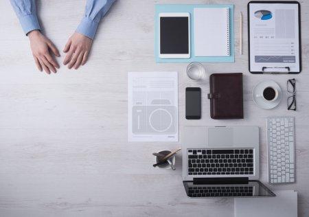 Photo pour Homme d'affaires travaillant au bureau, détail des mains avec copyspace et divers objets sur la droite, vue de dessus - image libre de droit