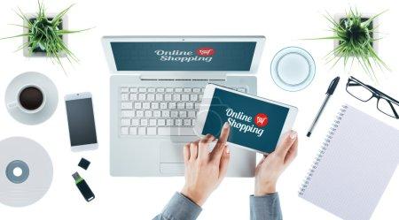 Photo pour Interface utilisateur d'achat en ligne sur ordinateur portable et tablette et mains féminines sur l'interface d'écran tactile, vue du dessus - image libre de droit