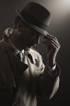 Photo pour Détective ajustant son chapeau restant dans l'obscurité, film noir - image libre de droit
