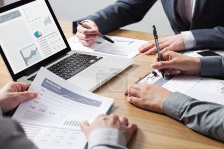 Photo pour Des professionnels de travailler ensemble au bureau, mains bouchent soulignant les données financières sur un rapport, la notion de travail d'équipe - image libre de droit