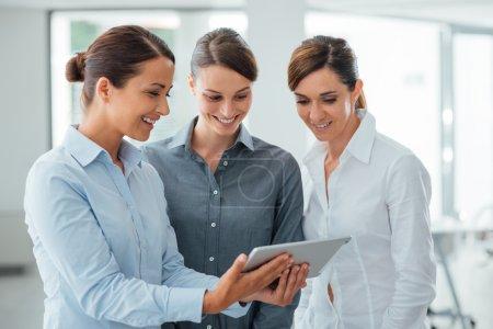 Photo pour Professionnel souriant femmes d'affaires permanent au bureau et à l'aide d'un comprimé d'écran tactile, ils sont appréciant et regarder l'écran - image libre de droit
