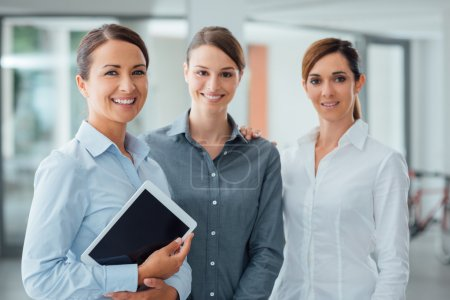 Photo for Professional smiling business women standing in the office and smiling at camera, one is holding a digital tablet - Royalty Free Image