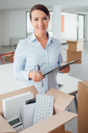 Photo for Smiling businesswoman writing a relocation checklist for her office on a clipboard and looking at camera, open carton box on foreground - Royalty Free Image