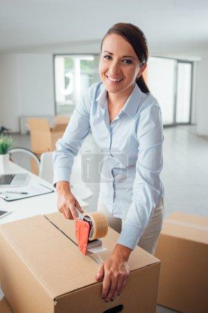 Businesswoman taping up  cardboard box