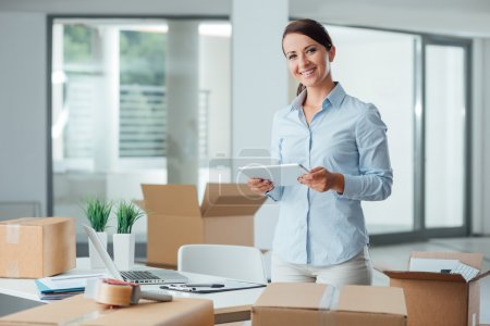 Photo for Confident smiling business woman moving in her new office, she is unpacking boxes and using a digital tablet - Royalty Free Image