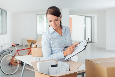 businesswoman writing a relocation checklist