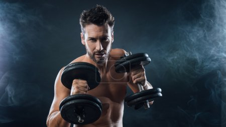 Photo for Attractive shirtless man exercising and lifting weights on dark background, strength concept - Royalty Free Image