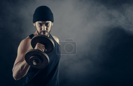 Photo for Cool confident man with cap lifting weights and working out - Royalty Free Image