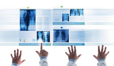 Photo pour Équipe médicale professionnelle examinant les dossiers médicaux du patient et les radiographies sur les diapositives à écran tactile, un médecin touche une icône et défilement - image libre de droit