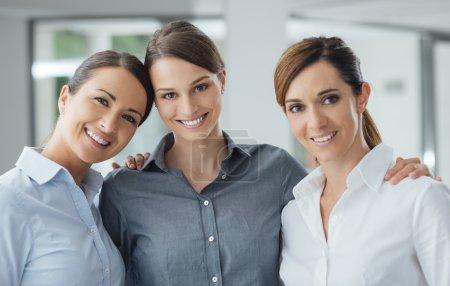 Foto de Mujeres posando juntos en la oficina y sonriendo en el concepto de empoderamiento de mujeres, trabajo en equipo y cámara - Imagen libre de derechos