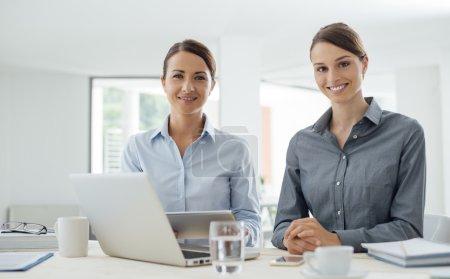 Photo pour Femmes d'affaires professionnelles assis au bureau et travaillant avec une tablette numérique, ils sourient à la caméra - image libre de droit
