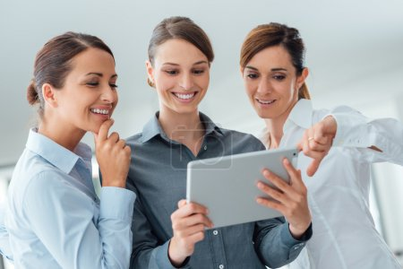 Photo for Professional smiling business team  standing in the office and using a touch screen tablet, they are enjoying and watching the screen - Royalty Free Image