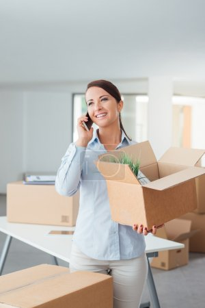 Photo for Beautiful smiling woman moving in a new office, talking on the phone - Royalty Free Image