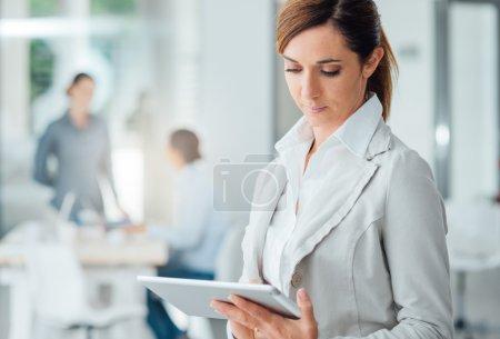 Photo pour Femme de confiance professionnelle permanent au bureau et à l'aide d'un comprimé d'écran tactile numérique - image libre de droit