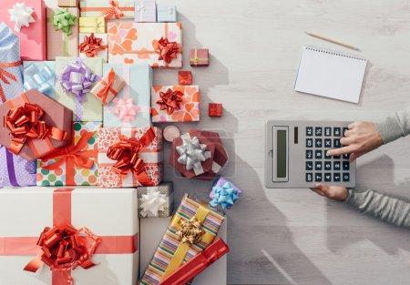 Photo pour Calcul des coûts de l'homme avec une calculatrice et beaucoup de boîtes à cadeaux colorés, concept cher de Noël - image libre de droit