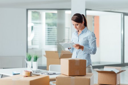 Photo for Confident business woman moving in her new office and using a digital tablet, she is surrounded by cardboard boxes - Royalty Free Image