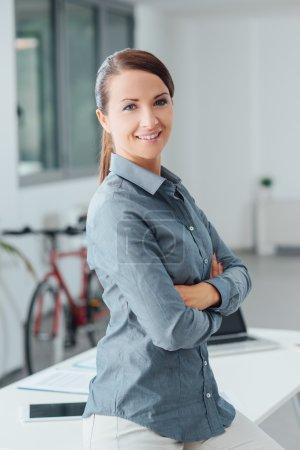 Foto de Mujer de negocios hermosa y segura en la oficina posando con los brazos cruzados y mirando a la cámara - Imagen libre de derechos