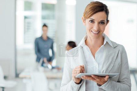 Photo pour Femme d'affaires souriante confiante debout dans le bureau et utilisant une tablette numérique à écran tactile - image libre de droit