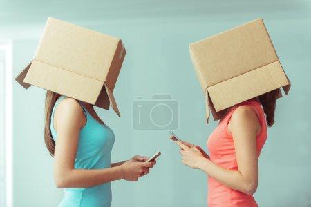 Foto de Adolescentes con cajas en sus mensajes de texto de jefes con sus teléfonos inteligentes, redes sociales y el concepto de aislamiento - Imagen libre de derechos