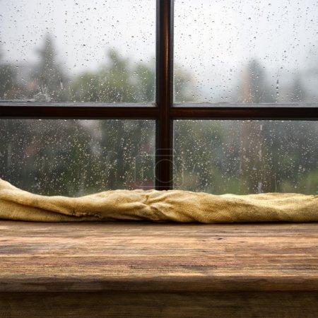 Photo pour Table vide pour les montages d'affichage de produits près de la fenêtre pluvieuse - image libre de droit