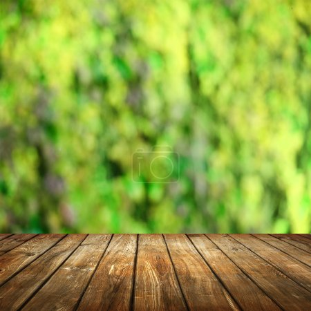 Empty table with blurred green  background