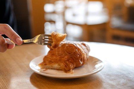Photo pour Image rapprochée de mains coupant un morceau de croissant à la fourchette pour le petit déjeuner sur une table en bois - image libre de droit