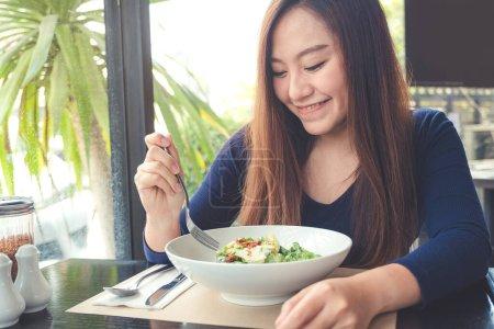 Photo pour Une femme asiatique à la recherche et profiter de manger salade de Ceasar au restaurant avec sentiment heureux - image libre de droit