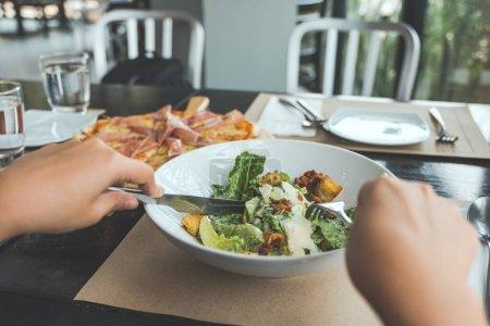 Photo pour Une main à l'aide d'une fourchette et d'un couteau pour manger la salade de Ceasar avec pizza sur la table à manger dans le restaurant - image libre de droit