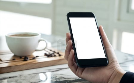 Photo pour Image de maquette de mains tenant un téléphone portable noir avec écran blanc vierge avec une tasse de café dans un café - image libre de droit
