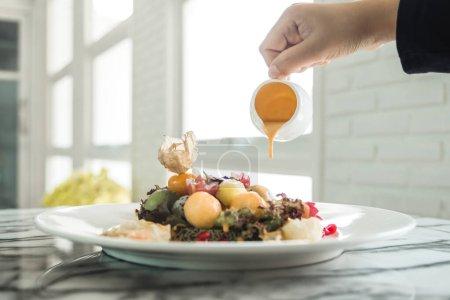 Photo pour Une main versant la sauce à la crème dans la salade de fruits mélangés dans le restaurant - image libre de droit