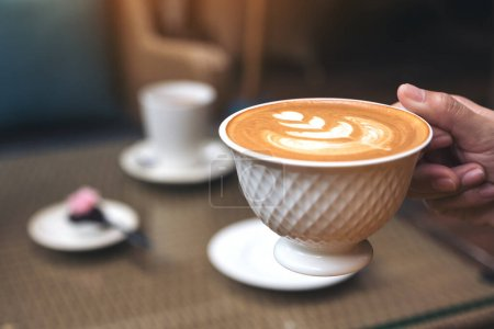 Photo pour Image rapprochée d'une main tenant une tasse de café latte chaud avec latte art dans le café - image libre de droit