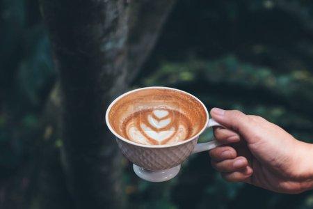 Photo pour Image rapprochée d'une main tenant une tasse de café chaud latte avec cœur latte art dans fond vert de la nature - image libre de droit