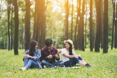 Photo for A group of young people playing ukulele while sitting together in the park - Royalty Free Image