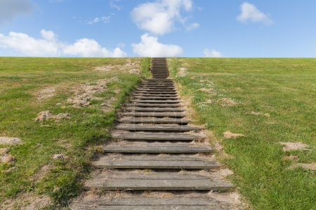 Photo for Wooden stairs upon green hill with a blue sky - Royalty Free Image