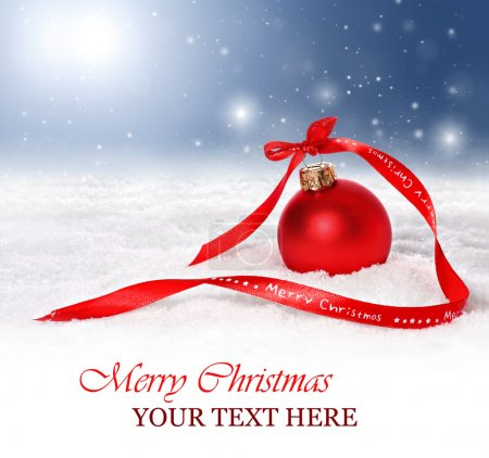 Christmas background with bauble and red merry christmas ribbon in snow