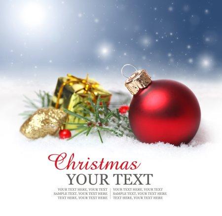 Photo pour Fond de Noël et de vacances avec ornement rouge, baies et sapin dans la neige - image libre de droit