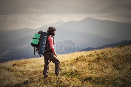 Photo for Young woman hiking on mountains with backpack Travel Lifestyle and outdoor recreation summer. Vacations concept. Filtered image:cross processed vintage effect. - Royalty Free Image