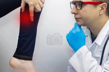 La mujer sufre de dolor en el ratón ternero. Concepto de tratamiento de rodilla para trauma, miositis, daño nervioso u osteoartritis. Médico examina