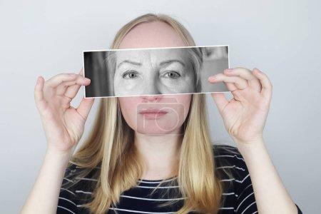 Photo pour La jeune fille tient sur son visage une photo de sa vieille mère. Vieillissement, génétique, arbre généalogique et perte du concept de jeunesse. Changements liés à l'âge avant et après. - image libre de droit