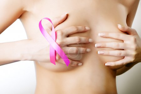 Breast cancer. Pink ribbon on a woman's breasts. Concept of medi