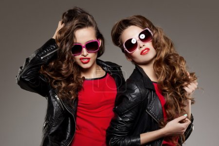Photo for Sisters twins in hipster sun glasses laughing Two fashion models Women smiling positive Friends group having fun, talking Youthful friendship youth adults people culture concept Young girls rock party - Royalty Free Image