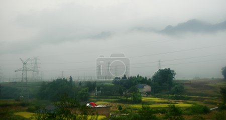 Photo pour Ligne de transport d'électricité dans la région montagneuse couverte de brume - image libre de droit
