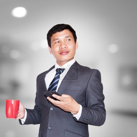 Asian businessman with cup of coffee and using smartphone looking away on blank space