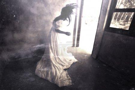 Photo pour Fantôme dans la maison hantée, femme mystérieuse en robe blanche debout dans l'immeuble Abandon, fond d'horreur pour Halloween Concept et idées de couverture de livre - image libre de droit