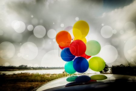 Colorful balloons on car roof