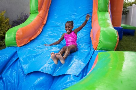 Happy little girl sliding down an inflatable bounce house.