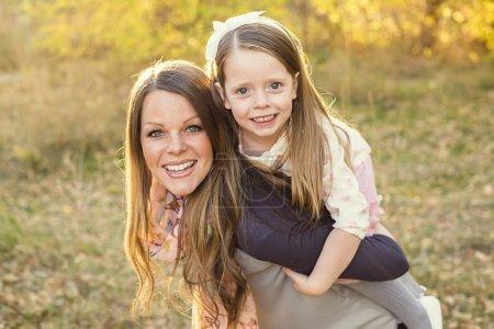 Photo pour Portrait d'une belle jeune mère et sa fille mignonne jouant dans le parc ensemble à l'extérieur un jour d'automne ensoleillé . - image libre de droit