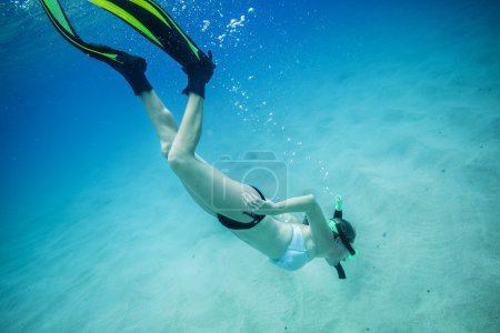 Underwater portrait of a woman snorkeling in clear tropical sea. She is diving below the surface to get a closer look at the sea life on the ocean floor